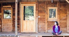 Une femme s'assied sur le porche d'une vieille maison en bois image libre de droits