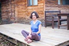 Une femme s'assied sur le porche d'une vieille maison en bois photos stock