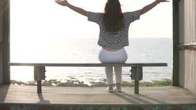 Une femme s'assied sur un banc par la mer banque de vidéos