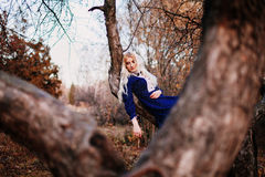 Une femme s'est habillée dans une robe bleue de vintage se repose sur la branche Image libre de droits