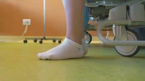 Une femme se lève d'un berceau d'hôpital banque de vidéos