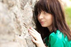 Une femme se penchant contre un mur en pierre Photographie stock