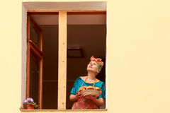 Une femme se tenant à la fenêtre, rêvant Images stock