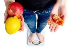 Une femme se tient sur des échelles dans les mains d'un centimètre de citron de pomme photo libre de droits