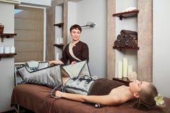 Une femme se trouvant vers le bas faisant le traitement pressotherapy image stock