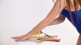 Une femme sexy dans un maillot de bain de bleu mesure les faisceaux en bois avec une bande de mesure la belle fille se déplace ér banque de vidéos