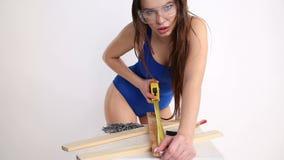 Une femme sexy dans un maillot de bain de bleu mesure les faisceaux en bois avec une bande de mesure la belle fille se déplace ér clips vidéos