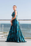 Une femme luxueuse dans une belle robe en soie verte sur le fond de ciel bleu Été, mer, océan, et concept de plage Photographie stock libre de droits