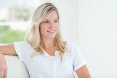 Une femme souriant légèrement comme elle regarde au loin au côté Photographie stock libre de droits