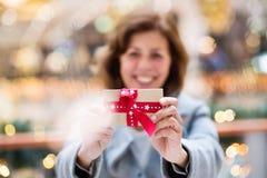 Une femme supérieure avec un présent au centre commercial au temps de Noël photographie stock libre de droits
