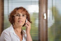 Une femme supérieure avec un téléphone Photos libres de droits