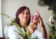 Une femme supérieure décorant un arbre de Noël à la maison photo libre de droits