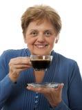 Une femme supérieure heureuse buvant une cuvette de café Photo libre de droits