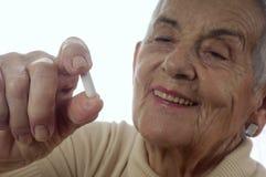 Une femme supérieure prenant des pilules Photographie stock libre de droits
