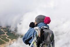 Une femme sur le dessus de la montagne photographiant un paysage de entre des nuages images libres de droits