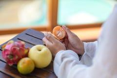 Une femme tenant et épluchant une orange pour manger avec la poire et le fruit du dragon sur une table photos libres de droits