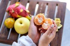 Une femme tenant et épluchant une orange pour manger avec la poire et le fruit du dragon sur une table photo stock