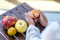 Une femme tenant et épluchant une orange pour manger avec la poire et le fruit du dragon sur une table photographie stock libre de droits