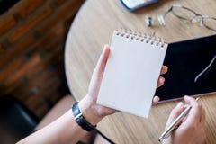Une femme tenant le carnet vide avec le comprimé sur la table en bois dans le bureau Photo stock