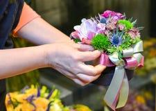 Une femme tenant un bouquet dans une petite case photographie stock
