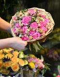 Une femme tenant un bouquet des roses enveloppées en papier photographie stock