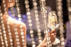 Une femme tenant un verre de champagne dans la réception l'épousant image libre de droits