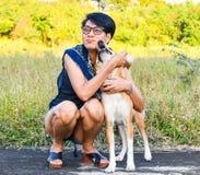Une femme thaïlandaise avec son chien jouant sur le champ d'herbe, ils sont regard très heureux et drôle photographie stock libre de droits