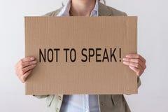 Une femme tient une bannière avec l'inscription POUR NE PAS PARLER images stock