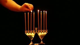Une femme tient une bougie dans sa main avec laquelle elle allume des bougies dans une lampe de Hanoucca