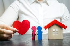 Une femme tient dans des ses mains un coeur rouge près d'une famille et d'une maison miniatures Le concept de l'assurance des bie photos libres de droits