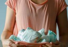 Une femme tient dans son T-shirt avec ses mains beaucoup de couche-culotte utilisée photos libres de droits