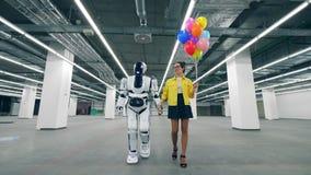 Une femme tient des ballons à disposition tout en marchant dans une chambre avec le cyborg banque de vidéos