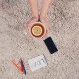 Une femme tient des mains par tasse de thé avec le citron, le téléphone, le stylo et le carnet se trouvant sur le tapis, vue supé Photos libres de droits