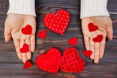 Une femme tient un coeur rouge dans des ses mains Concept d'amour Photos stock