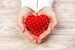 Une femme tient un coeur rouge dans des ses mains Concept d'amour Photographie stock