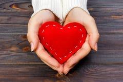 Une femme tient un coeur rouge dans des ses mains Concept d'amour Photo libre de droits
