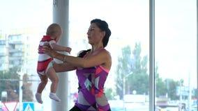 Une femme tient un enfant sur ses bras et postures accroupies, s'exerçant pour des mères banque de vidéos