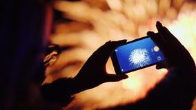 Une femme tire des feux d'artifice sur un smartphone Les lumières sont admirablement réfléchies en ses verres Images stock