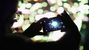 Une femme tire des feux d'artifice sur un smartphone Les lumières sont admirablement réfléchies en ses verres Image stock