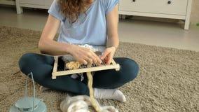 Une femme tisse sur un métier à tisser qu'une belle broderie a fait du fil, dans un studio à la maison, banque de vidéos