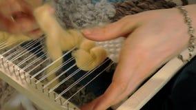 Une femme tisse sur un métier à tisser qu'une belle broderie a fait du fil, dans un studio à la maison, clips vidéos