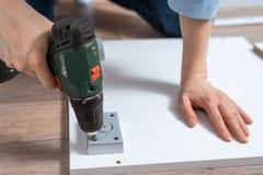 Une femme tord un meuble utilisant un plan rapproché de tournevis, Assemblée de meubles photographie stock