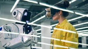 Une femme touche la main du robot tout en portant des lunettes de VR banque de vidéos