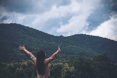 Une femme tournent de retour et ont étiré les bras avec le ciel bleu, la nature verte et la montagne Image stock