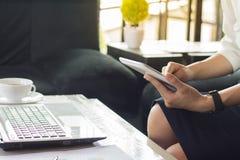 Une femme travaillant dans un bureau avec un téléphone portable et un ordinateur photographie stock
