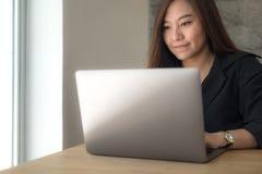 Une femme travaillant et dactylographiant sur l'ordinateur portable sur la table en bois dans le bureau Images stock