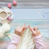 Une femme tricote un tissu tricoté par blanc de fil de laine Blac de café Photographie stock libre de droits