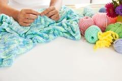 Une femme tricote un tissu tricoté par vert de fil épais Photographie stock