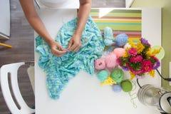 Une femme tricote un tissu tricoté par vert de fil épais Photo libre de droits