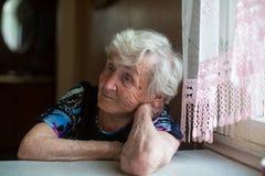 Une femme triste pluse âgé s'assied pensivement à la table photos stock
